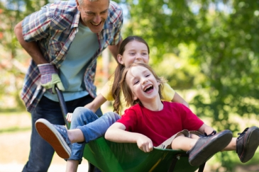 father push children in wheelbarrow